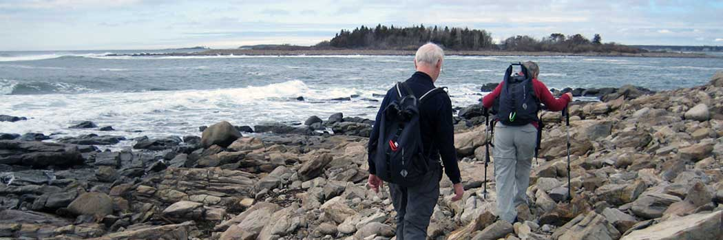 People walking on rocky Maine shoreline